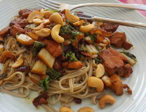 Bruine rijstnoodles met kip, paksoy en cashewnoten